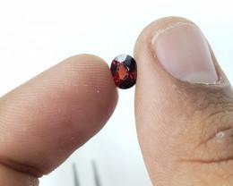 Slight oval small garnet gem   glistening, beautiful red,