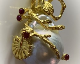 A BAROQUE PEARL AND RUBY GOLD AND STERLING SILVER .925 PENDANT