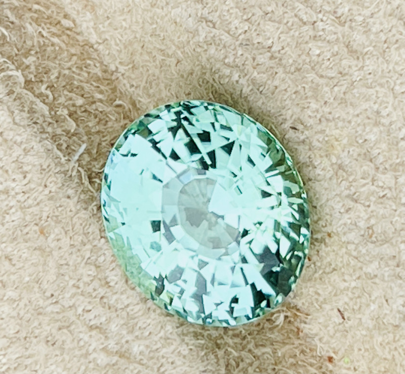 Very bright bluish green tourmaline.  Highly reflective.   Photos taken outside and it's snowing lightly.