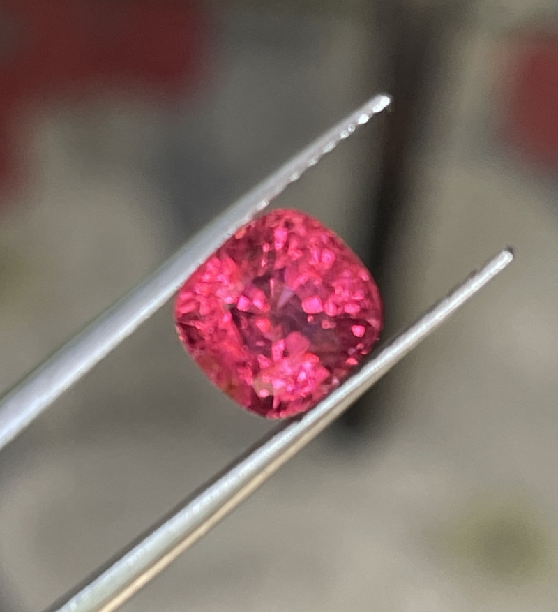Red pink spinel.   Very pretty color!    Bright reflection from high quality cutting.    No open window. All video and photos taken in natural shaded light.