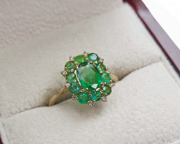 Beautiful ring with central emerald and side emeralds and diamonds.