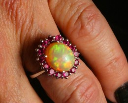 Stunning Sunset colored Ethiopian opal ring with halo of  Burmese Ruby. 18 ct White gold. Created by opal ring designer Amy Klitsner.